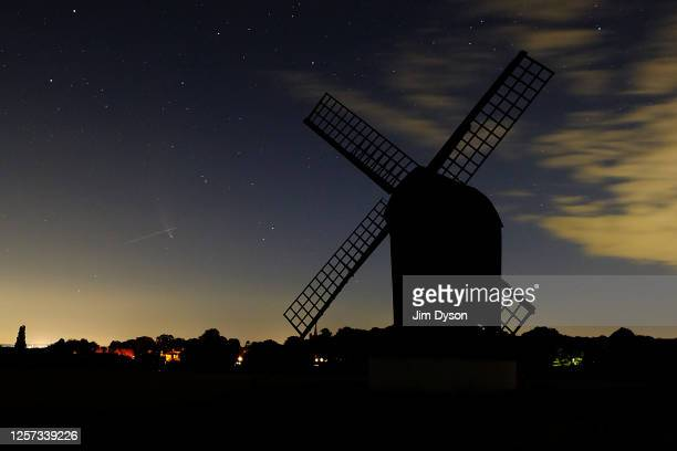 The Comet NEOWISE is crossed by a meteor in the sky behind Pitstone Windmill on July 20 2020 in Ivinghoe United Kingdom The comet is named after...