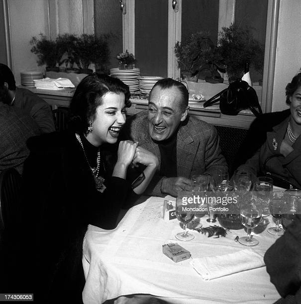 The comic actor from Naples Antonio de Curtis known as Totò is laughing at the table of a restaurant with his daughter Liliana and his partner the...