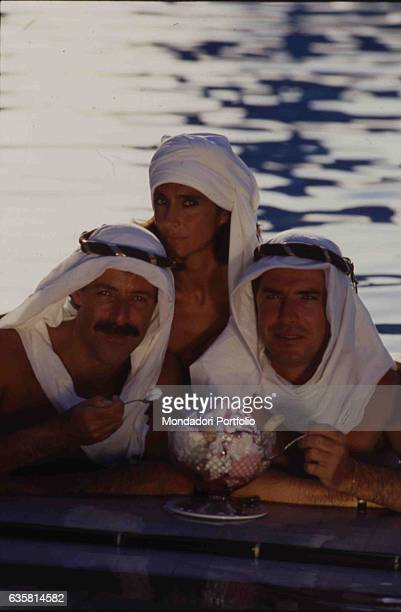 The comic trio formed by Massimo Lopez, Anna Marchesini and Tullio Solenghi posing by a swimming pool in front of a huge ice-cream cup. On their...