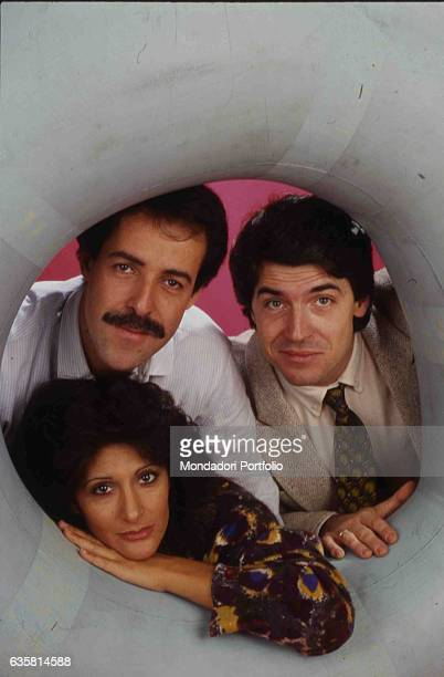 The comic trio formed by Massimo Lopez, Anna Marchesini and Tullio Solenghi peeping out from a big life buoy for a photo shooting. Italy, 1985