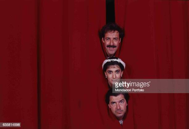 The comic trio formed by Massimo Lopez, Anna Marchesini and Tullio Solenghi peeping out from the red curtain in the theatre show 'In principio era il...