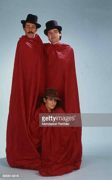 The comic trio formed by Massimo Lopez, Anna Marchesini and Tullio Solenghi posing wrapped in a huge red sheet, with hats. Italy, 1990