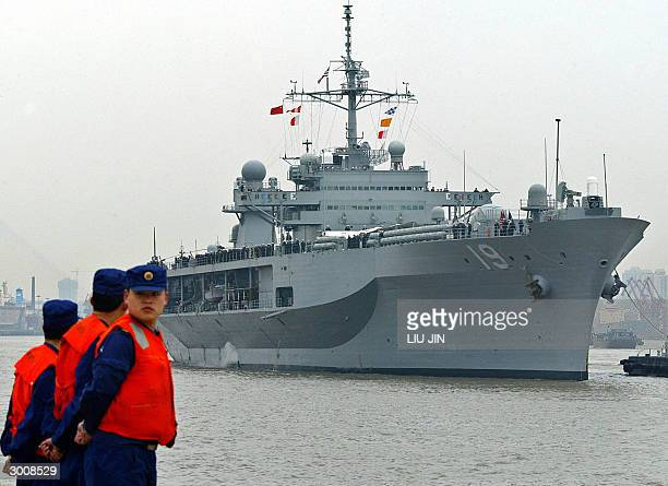 The command ship of the US Navy's Seventh Fleet, the USS Blue Ridge sails along the Huangpu river as the Chinese navy soldiers stands guard in...
