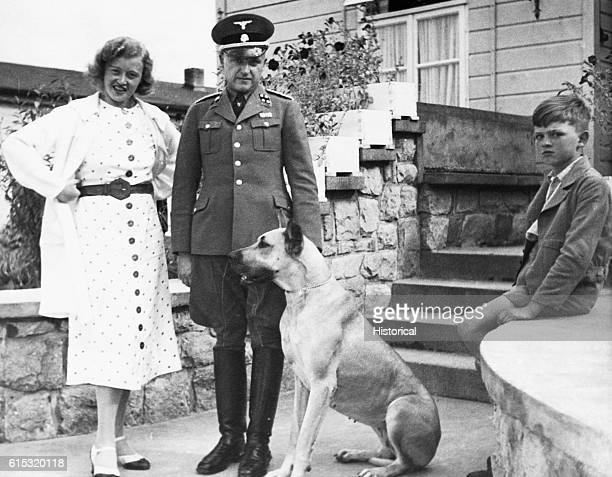 The commandant of the Buchenwald Concentration Camp SS Colonel Karl Koch stands with his wife Ilsa their son and dog