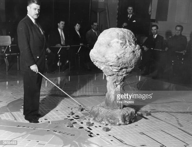 The commandant of the Civil Defence Technical Training Centre in Quebec demonstrates the effect of an atomic bomb exploding over a city Canada 28th...