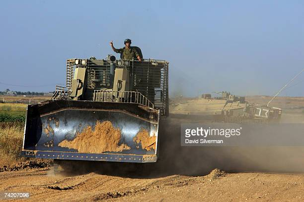 The commander of an Israeli army armored bulldozer gestures as it travels in convoy along the IsraelGaza border after leaving the Gaza Strip May 21...