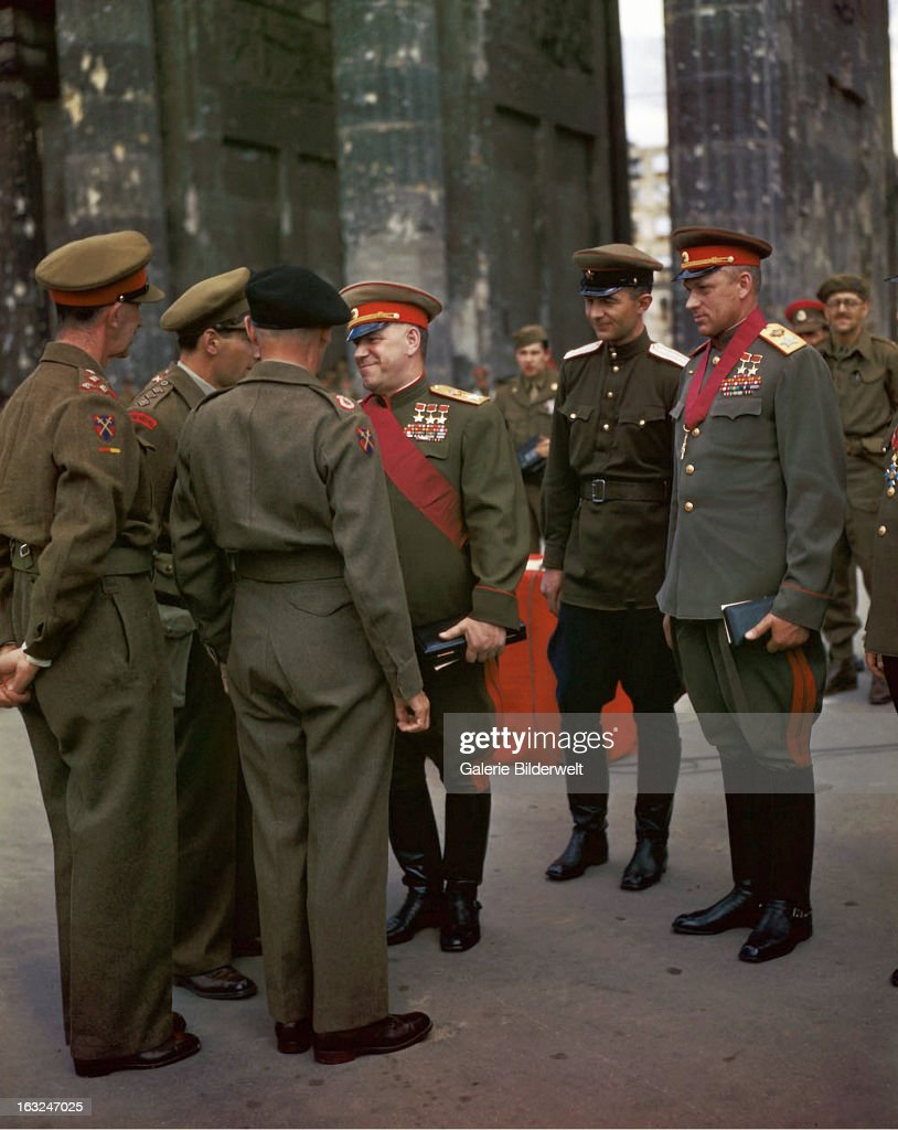 The Commander of the 21st Army Group, Field Marshall Sir Bernard Montgomery (1887 - 1976) - 2nd from left - and the deputy Supreme Commander in Chief of the Red Army, Marshal Georgy K. Zhukov (1896 - 1974) - 3rd from left - are talking with a British officer after medals have been awarded by Field Marshall Sir Bernard Montgomery to Russian generals at Brandenburg Gate. Marshal Konstantin Rokossovsky (1896 - 1968) - right - and other officers are watching. 12th July 1945. Berlin, Germany.