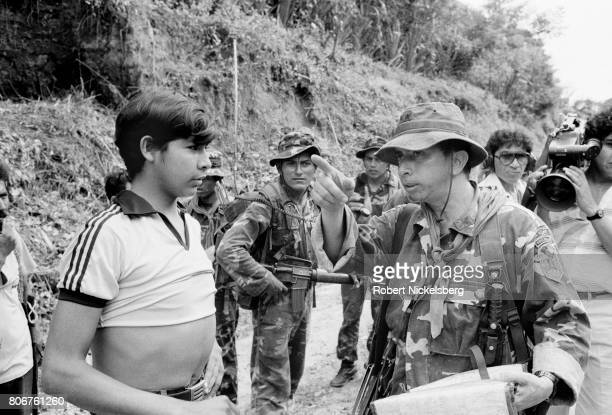 The commanding officer of the Atlacatl Battalion, Lt Col Domingo Monterrosa, right, questions a local resident, left, as his forces advance during a...
