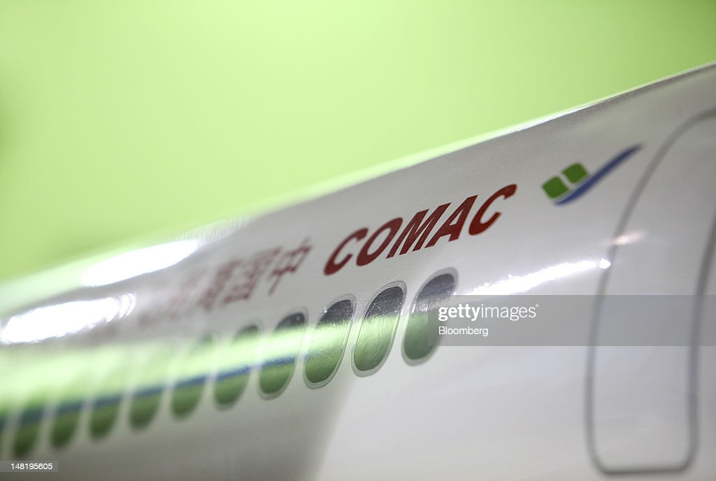 The Commercial Aircraft Corp. of China (Comac) logo sits onthe fuselage of a model aircraft on the company's stand on the third day of the Farnborough International Air Show in Farnborough, U.K., on Wednesday, July 11, 2012. The Farnborough International Air Show runs from July 9-15. Photographer: Chris Ratcliffe/Bloomberg via Getty Images