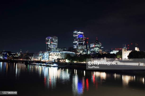The commercial towers of the City of London financial district and Tower of London stand on the north side of the River Thames shortly after midnight...