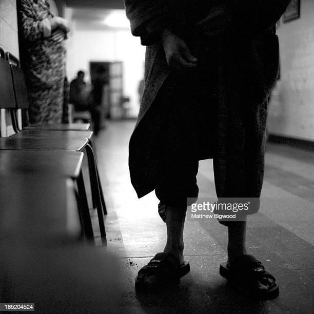 CONTENT] The communal corridor in a Romanian psychiatric hospital The feet of one of the patients wearing light shoes is visible on the cold stone...