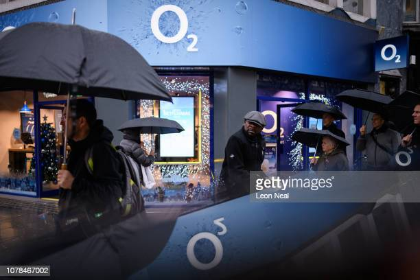 The company logo is reflected in a mobile phone screen as shoppers walk past a branch of the o2 mobile network store on December 06 2018 in London...