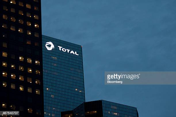 The company logo sits illuminated outside the headquarters of Total SA in La Defense business district in Paris France on Thursday Feb 6 2014...