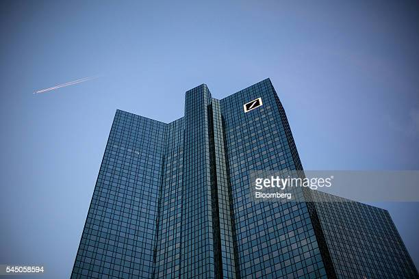 The company logo sits on one of the twin tower skyscrapers of the headquarter offices of Deutsche Bank AG at dusk in the financial district in...