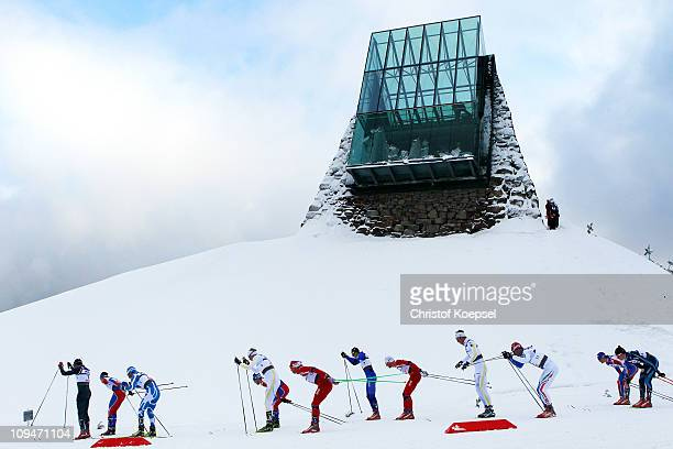 The competitors pass the tower of the HS 106 ski jump in the Men's Cross Country 30km Pursuit race during the FIS Nordic World Ski Championships at...
