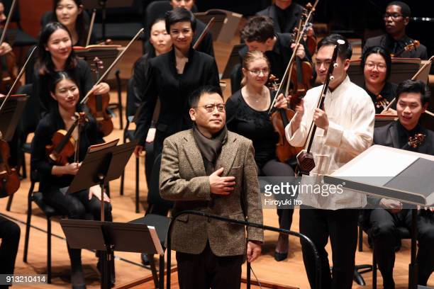 The composer Guo Wenjing center the conductor Chen Lin standing behind him and the Erhu player WeiYang Andy Lin right taking a bow after WeiYang Andy...
