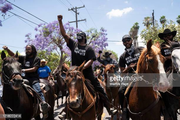The Compton Cowboys raise their fists in the air during a 'peace ride' for George Floyd on June 7, 2020 in Compton, California. This is the 13th day...