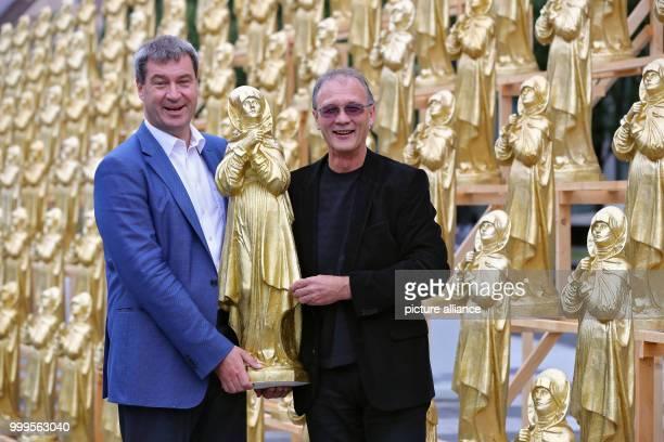 The concept artist Ottmar Hoerl and the Bavarian minister of homeland affiars Markus Soeder stand between golden Madonna figurines in Nuremberg...