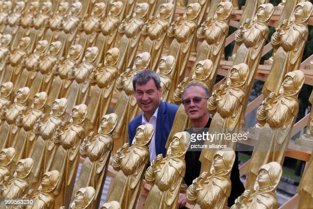 The concept artist Ottmar Hoerl and the Bavarian minister of homeland affairs Markus Soeder stand between golden Madonna figurines in Nuremberg...