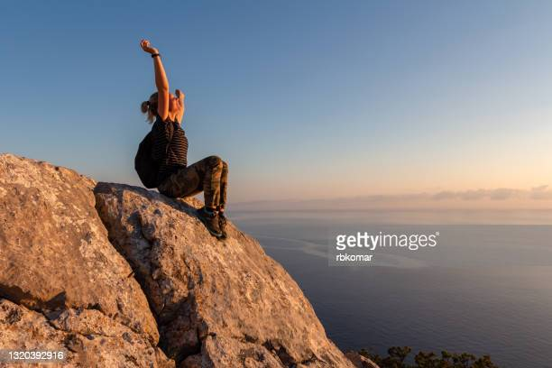 the concept of independence, freedom and motivation. winner girl on top of the mountain - cliff stock pictures, royalty-free photos & images