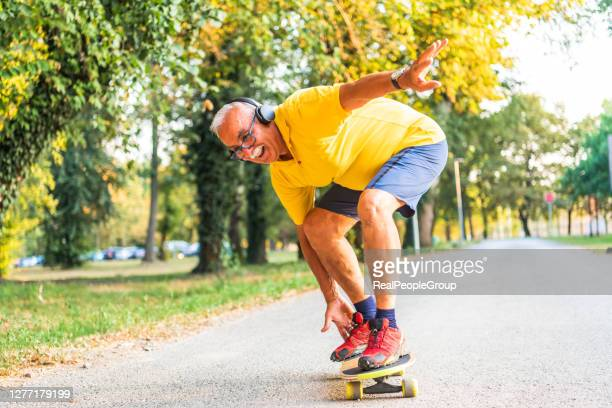 the concept of life satisfaction. portrait of a positive gray-haired man with a skateboard. winner concept. - skating stock pictures, royalty-free photos & images