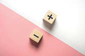 The concept of opposites, wood blog with plus and minus on white and pink background.