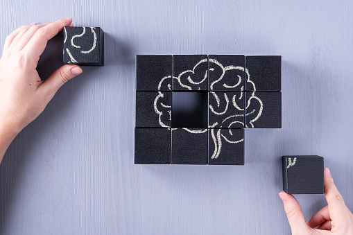 The concept of the human brain. Education, science and medical concept.  Brain drawn in chalk on black cubes. 1129860760