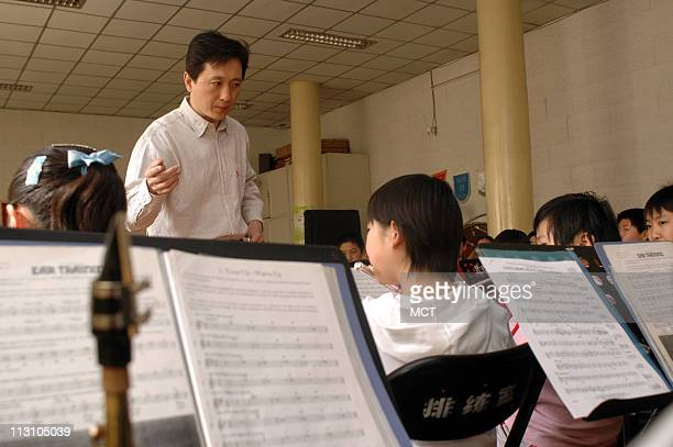 The conductor for a children's weekend orchestra class held at the Jingshan Shaonian Gong Chen Tong instructs the flute players to perform April 16...