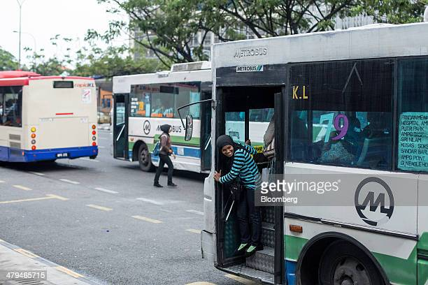 The conductor of a bus operated by Metrobus Nationwide Sdn. Bhd. Waits for passengers in Kuala Lumpur, Malaysia, on Tuesday, March 18, 2014....