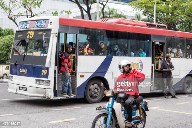 The conductor of a bus operated by Rapid Bus Sdn. Bhd. Calls for passengers in Kuala Lumpur, Malaysia, on Tuesday, March 18, 2014. Malaysia, aspiring...