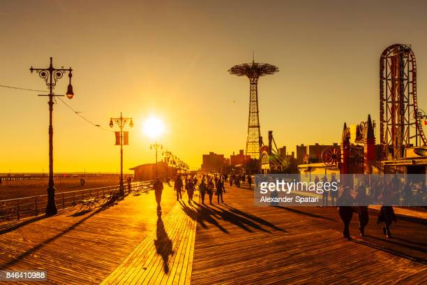 the coney island boardwalk at sunset, brighton beach, brooklyn, new york city, ny, usa - boardwalk stock pictures, royalty-free photos & images