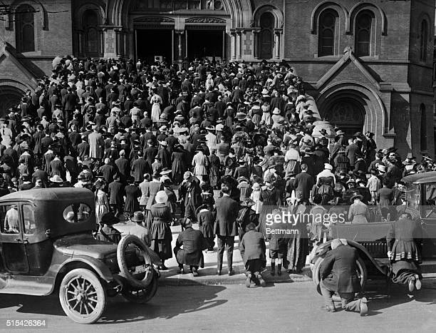 The congregation praying on the steps of the Cathedral of Saint Mary of the Assumption where they gathered to hear mass and pray during the influenza...
