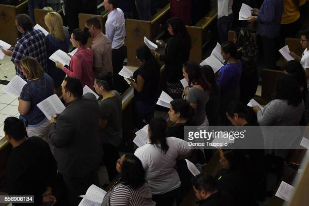 The congregation sing hymns during a vigil at Guardian Angel Cathedral for the victims of the Route 91 Harvest country music festival shootings on...