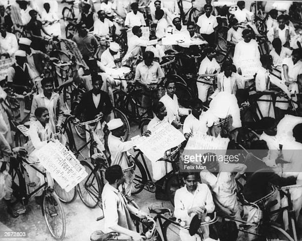 The Congress Party's general strike in Bombay in protest against the Constitutional reforms introduced in April. Cyclists carry placards which read...