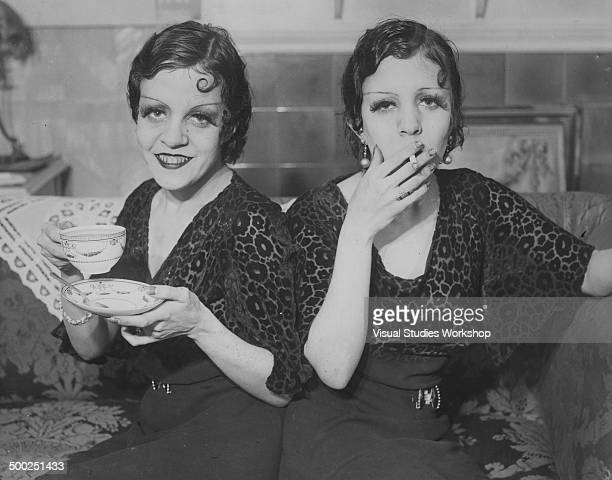 The conjoined English Hilton sisters who can sing dance and are accomplished musicians pose on a couch London England early to mid 20th century From...