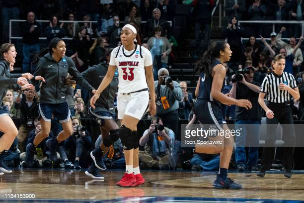 The Connecticut Huskies bench storm the court after winning the game as Louisville Cardinals Forward Bionca Dunham returns to her bench on March 31...