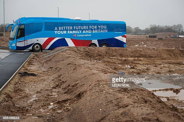 The Conservative Party election battle bus is seen between muddy fields during a general election campaign visit to a housing development in Chorley...