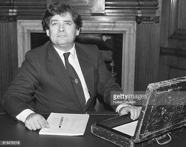 The Conservative politician and Chancellor of the Exchequer Nigel Lawson sits with his budget box