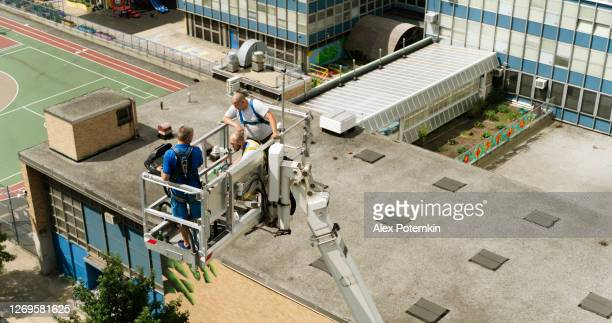 the construction team preparing for the high-altitude job using the lifting platform. harlem, new york city - roof stock pictures, royalty-free photos & images