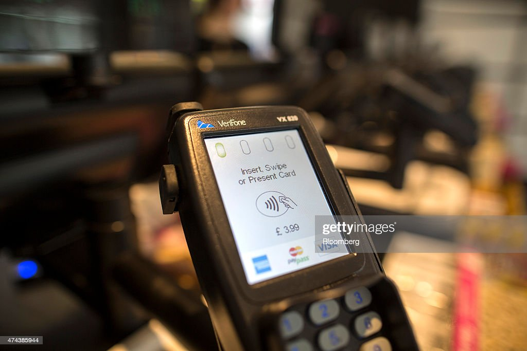 The contactless payment logo and the American Express Co., MasterCard Inc. and Visa Inc. logos are seen on a Verifone Systems Inc. payment device in London, U.K., on Friday, May 22, 2015. Credit and debit cards that can be used by tapping the reader are gaining users, and mobile apps are set to further boost the popularity of contactless paying. Photographer: Simon Dawson/Bloomberg via Getty Images