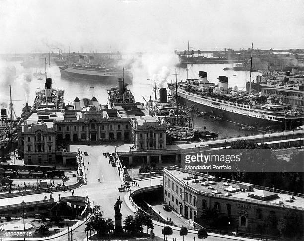 The Conte di Savoia transatlantic going to leave the Port nearby the harbour station. Genoa, 1939