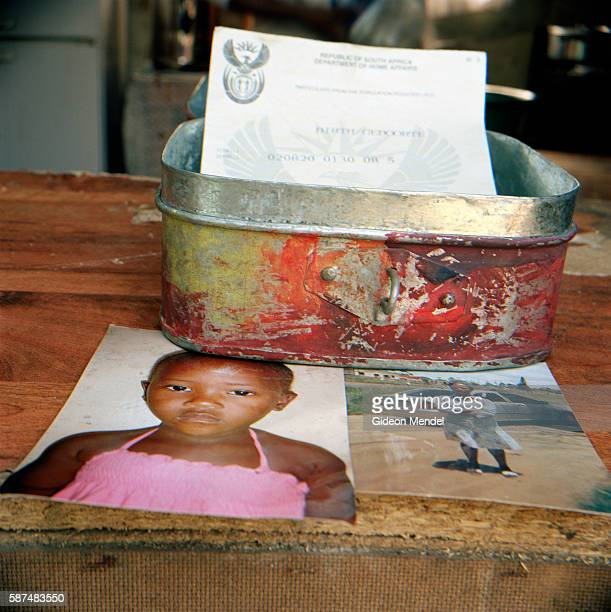 The contents of the memory box belonging to four year old Athenkosi Mthembu her birth certificate a snapshot of her and her mother Zamathembu Mthembu...