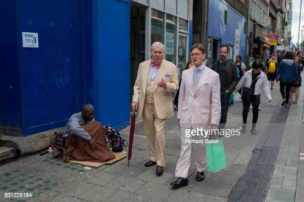 The contrast between two stylishlydressed gentelmen walking past a homeless man begging on Oxford Street on 10th August 2017 in London England
