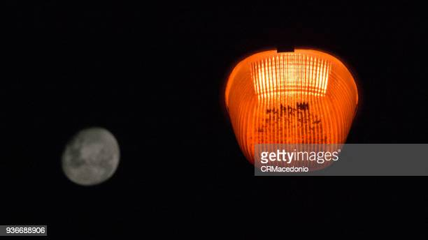 the contrast of public lighting with the full moon - crmacedonio stock photos and pictures