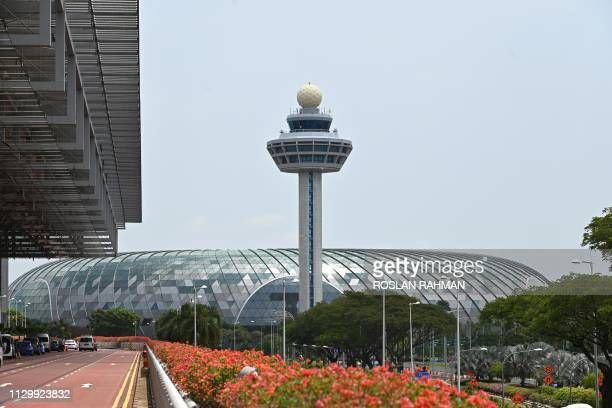 The control tower of Changi International Airport in Singapore is seen on March 12 2019 with the departure terminal at left and the newly constructed...