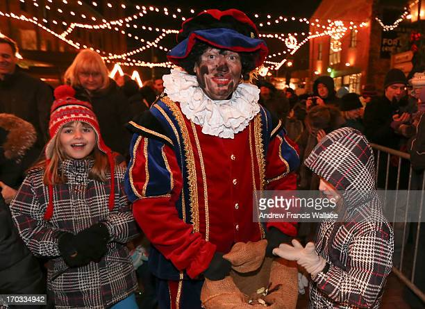 The controversial 'Black Pete' gives out candy to children at the Sinterklaas parade in the Distilary District December 5 2012 The tradition...