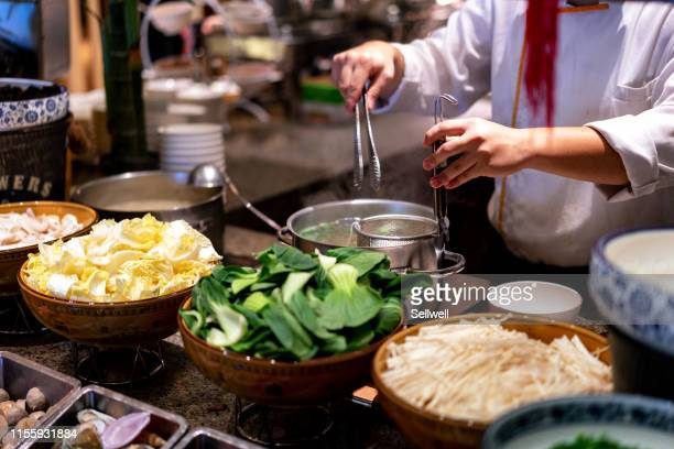 the cook is cooking boiled noodles and vegetables - asian food stock pictures, royalty-free photos & images