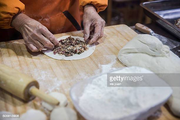 the cook making shaobing in the kitchen - hangzhou stock photos and pictures