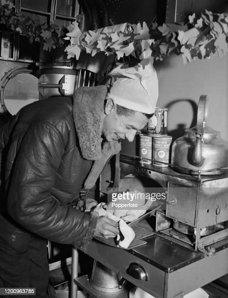 The cook of a Short Sunderland flying boat patrol bomber from Royal Air Force Coastal Command prepares a chicken for cooking in the onboard oven for...
