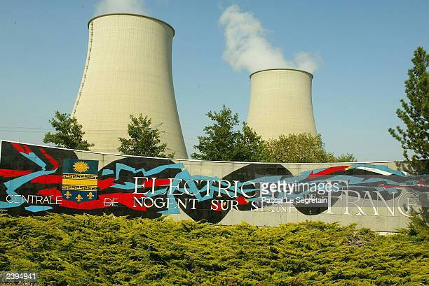 The cooling towers of the nuclear station of NogentsurSeine are seen behind the logo of the French government owned electricity board on August 12...